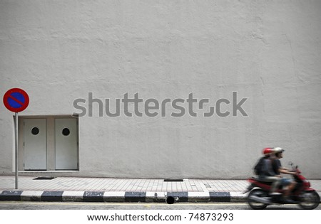 An empty concrete wall with copyspace for text along a street with a motorbike driving by.