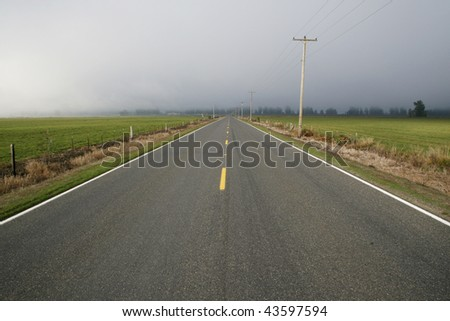 An empty country road with a storm approaching.
