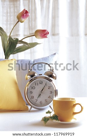 an empty cup, a metalic clock, and a vase with two tulips