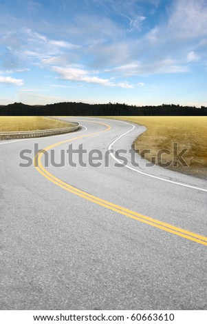 An empty curved road leading off into the horizon of trees and countryside.