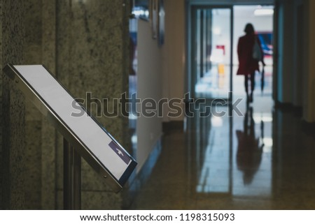 An empty directional sign with an arrow, directing towards a direction where someone is already going. Woman walking through a hall with a sign showing the way. #1198315093