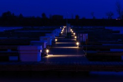 An empty dock in a yacht club is dimly illuminated an an Autumn evening in Toronto (Etobicoke), Ontario.