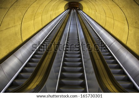 An empty escalator moves through oval tube of light to the Washington D.C. Metrorail commuter trains