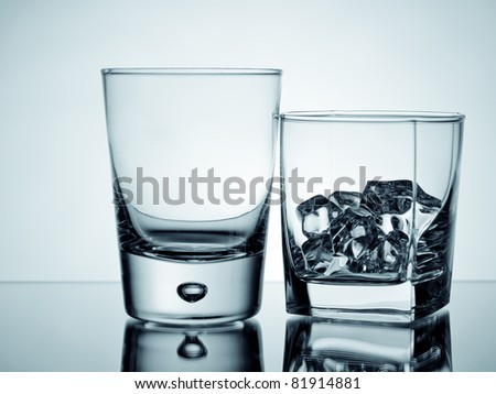 An empty glass and a tumbler with ice cubes - stock photo