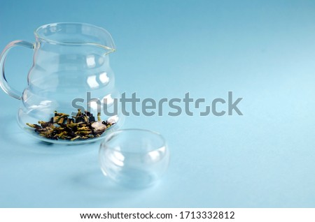 An empty glass teapot with blue tea clitoris flowers stands on a blue background. Space for text