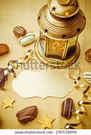 An empty golden seal to write headline. Ramadan lamp, date chocolates and confetti background.