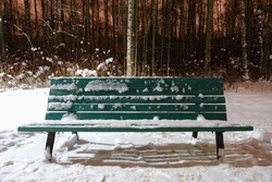 an empty green wooden bench covered with white snow and ice after a snowfall stands alone in the cold winter park at night on the background of snow-covered trees in the forest outdoors
