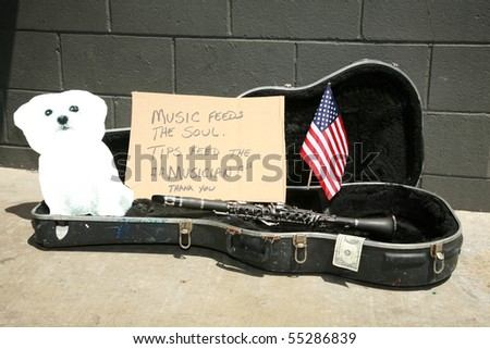 an empty guitar case with a sign and a cardboard cut out of a bichon frise dog asking for tips to play music