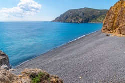 An empty hidden volcanic beach with black pebbles between rocks and blue calm water. A natural bay at the island of Chios in Greece. Natural sea background