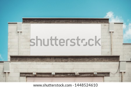 An empty huge poster mockup on the roof of a shopping mall or a cinema; a white template placeholder of an advert billboard on the rooftop of a building; blank mock-up of an outdoor information banner