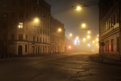 An empty illuminated asphalt road through the old historical buildings and houses in a fog at night. Street lights (lanterns) close-up. Riga, Latvia. Dark cityscape