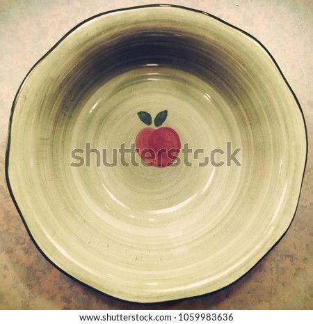 An empty light green bowl with cherry pattern on it on the table. #1059983636
