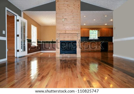 An empty living area with a fireplace.  Behind it is the dining and kitchen area.