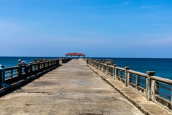 An empty local concrete pier with blue sky and Andaman sea as background