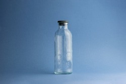 an empty measuring glass bottle of 250 milliliters with a scale of 50 milliliters from a dropper or other medicine stands with a black cap on a classic blue background