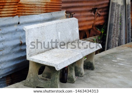 An empty old stone bench on rough ground cement with rusty zinc wall background  #1463434313