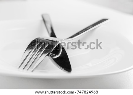 An empty plate, fork and knife lie crosswise on a white background. The dish did not like table etiquette #747824968