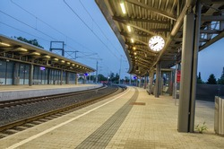 An empty railway station with a clock in evening.