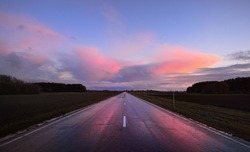 An empty rural road through the fields after the rain at sunset. Dramatic colorful sky, epic cloudscape. Latvia