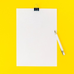 An empty sheet of paper is fastened with a stationery clip and a white pen on a yellow background. Mockup, blank for board announcement, information, statement, school. Top view, flat lay.