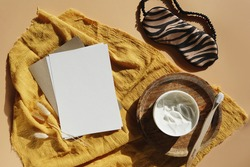 An empty sheet of white paper, cream, tooth brush, a sleeping mask on a yellow fabric on a pastel surface. A blank greeting card, mock up.