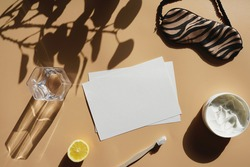 An empty sheet of white paper surrounded by container with cream, a lemon, tooth brush, sleeping mask and a glass on yellow surface, a mockup