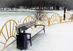 An empty snow-covered bench in the park against a yellow fence. The concept of winter solitude, the absence of people.