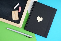 An empty space on a note book with blackboard, chalk, duster