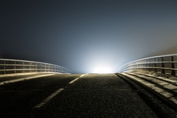 An empty spooky road on a winters night with a mysterious UFO glow just below the horizon.