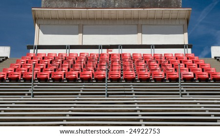 An empty stadium section with bleachers, reserved seats, and a press box