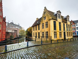 An empty street in a historical center of Ghent city near the St Bavo's Cathedral on a rainy day. A bridge through the canal. Traditional architecture. Travel guide, sightseeing theme. Belgium