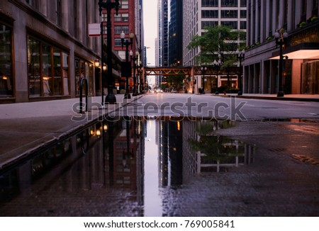 An empty street in downtown Chicago  is filled with a  large puddle. Inside the puddle, the buildings and lights reflect off the water. In the distance is the city traintracks.