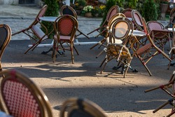 An empty summer outdoor area of a restaurant or cafe in a historic downtown is closed during lockdown. Tables and chairs without visitors. Challenging times business in HoReCa during a pandemic.
