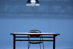 An empty Table and chair with hanging light bulb in room,  Investigation room concept