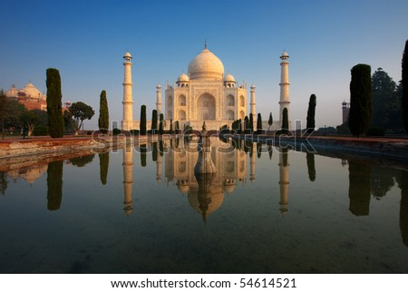 An empty Taj Mahal glows beautifully at sunrise as it's reflected in a calm water fountain.