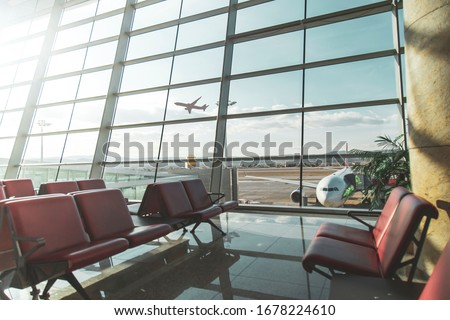 An empty terminal, aircrafts are waiting and preparing for their next flight and one of them taken off
