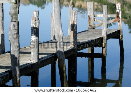 An empty wharf pier on a calm river in New Zealand .