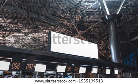 An empty white advertising or information billboard mock-up on the top of check-in and baggage claim area of a modern airport terminal, with multiple numbered counters and blank info screens below