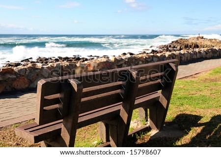 An empty wooden bench next to a pathway that runs next to a rocky shore, on a sunny Winters day.