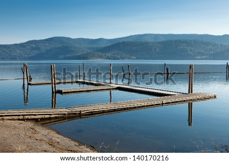 An empty wooden boat dock in late summer with haze around the mountains across the calm lake.