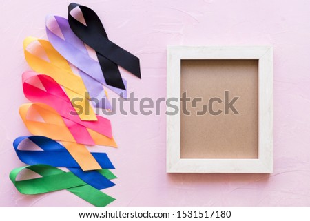 An empty wooden frame with colorful awareness ribbon on pink background