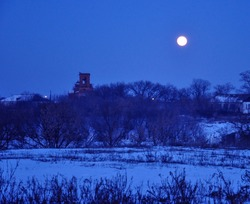 An enchanting night landscape with a full moon in the early spring outdoors
