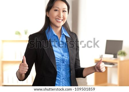 An energetic cute young Asian woman with enthusiastic expression wearing a black suit and blue shirt.
