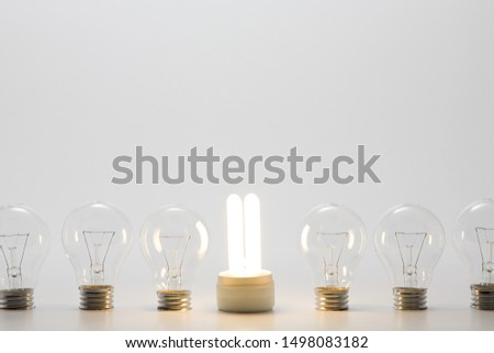 An energy saving lightbulb and ordinary lightbulbs