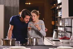An engaged couple cook together and have fun while tasting the sauce they have prepared. The married couple embraces to show their love. Concept of: cooking, love, lifestyle.