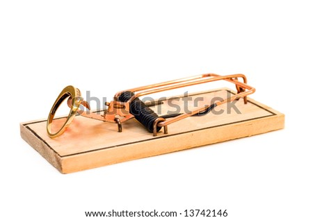 An engagement ring set on a mouse trap, isolated on a white background