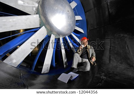 An engineer, checking up on the mechanical structure inside a wind tunnel