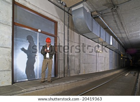 An Engineer in a dimly lit public transportation tunnel checking his Personal Digital Assistant