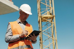 An engineer in an orange vest and a white construction control helmet conducts an inspection with a tablet in his hands against the background of a construction site and a tower crane