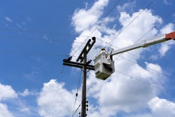 An engineer or electrician is working on a bucket. To repair high-voltage transmission lines.